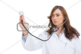 Serious pretty doctor holding stethoscope