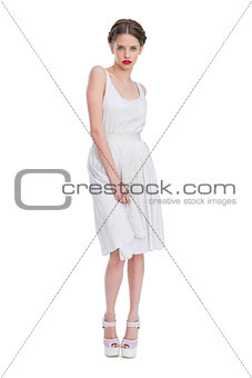 Attractive woman wearing white summer dress standing