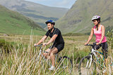 Athletic couple biking through countryside