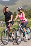 Happy couple on a bike ride with man pointing
