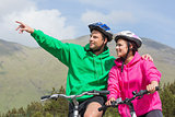 Smiling couple on a bike ride wearing hooded jumpers with man pointing