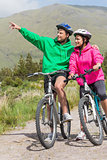 Athletic couple on a bike ride wearing hooded jumpers with man pointing