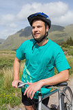 Fit man leaning on his mountain bike
