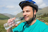 Fit man wearing helmet drinking water