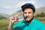 Fit man wearing bike helmet drinking water