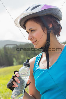 Fit woman wearing bike helmet holding water bottle