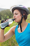 Fit woman wearing bike helmet drinking water