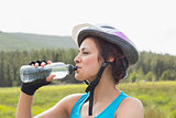 Athletic woman wearing bike helmet drinking water