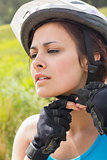 Athletic woman adjusting her bike helmet