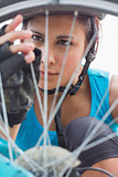 Focused woman adjusting her spokes on bike wheel