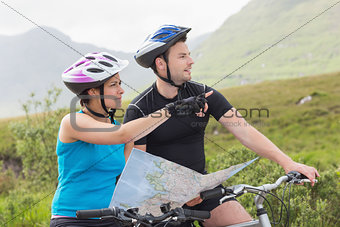 Couple on mountain bikes holding map and pointing