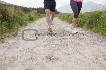 Couples feet running on a trail