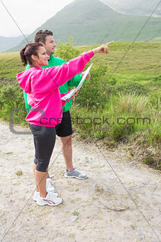 Couple holding a map and pointing ahead