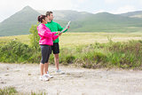 Athletic couple holding a map and looking ahead