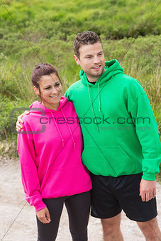 Athletic couple looking ahead and embracing