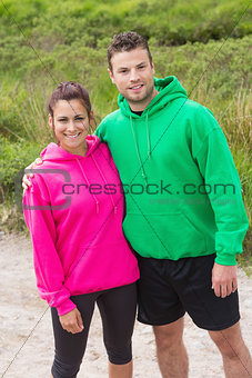 Athletic couple looking at camera and embracing