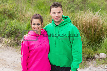 Fit couple looking at camera and embracing
