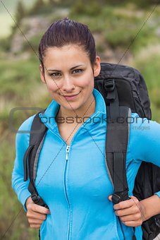Smiling female hiker with backpack looking at camera