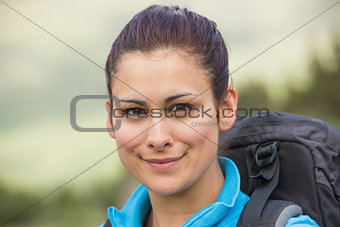 Female hiker with backpack smiling at camera