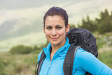 Attractive female hiker with backpack smiling at camera