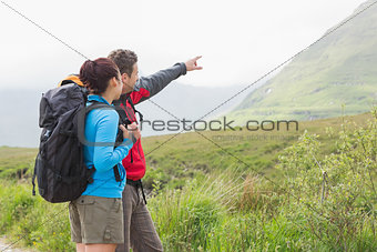 Couple of hikers with backpacks pointing at mountain
