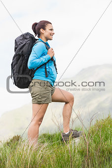 Attractive hiker with backpack walking uphill