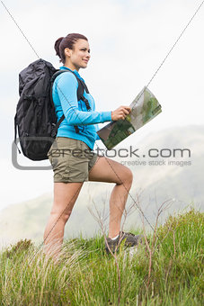 Attractive hiker with backpack walking uphill holding a map