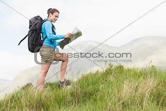 Attractive hiker with backpack walking uphill reading a map