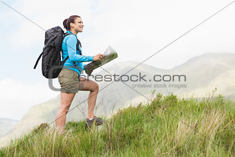 Attractive hiker with backpack hiking uphill holding a map