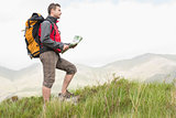 Handsome hiker with backpack hiking uphill holding a map