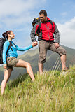 Handsome hiker helping his girlfriend uphill