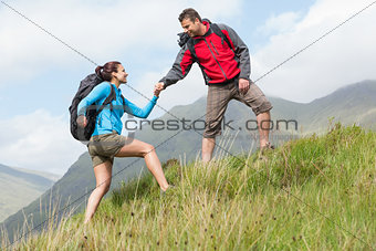 Attractive hiker helping his girlfriend uphill