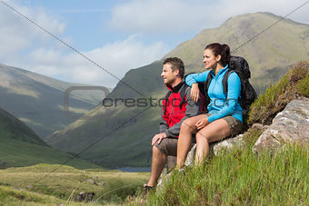 Couple taking a break after hiking uphill