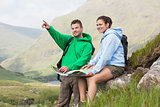 Couple resting after hiking uphill and consulting map