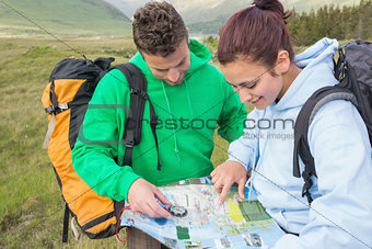 Couple sitting after hiking uphill and consulting map