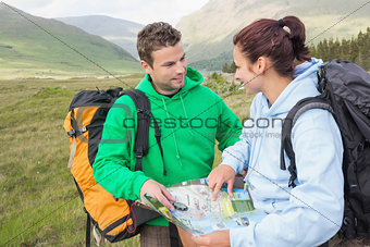 Happy couple resting after hiking uphill and consulting map