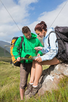 Attractive couple resting after hiking uphill and consulting map
