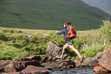 Athletic hiker leaping across rocks in a river