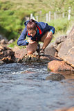 Hiker bending to take a drink from the stream