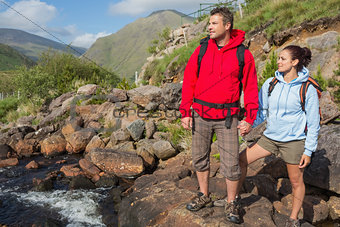 Couple standing at edge of river on a hike