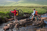 Couple crossing a river holding their bikes