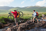 Couple crossing a stream holding their bikes