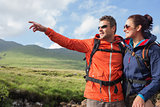 Couple wearing rain jackets and sunglasses admiring the scenery with man pointing