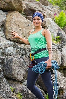Attractive female rock climber smiling at camera