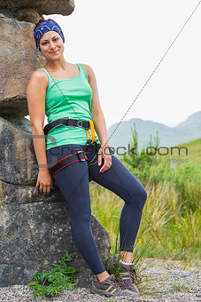 Attractive female rock climber leaning on rock face smiling at camera
