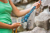 Female rock climber adjusting harness