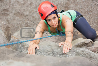 Determined girl climbing rock face
