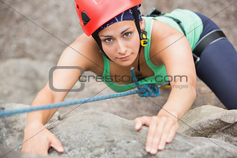 Focused girl climbing rock face