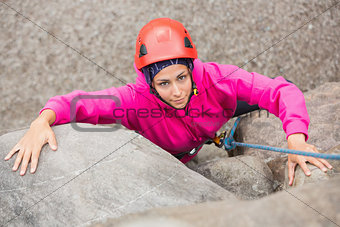 Smiling girl climbing up rock face
