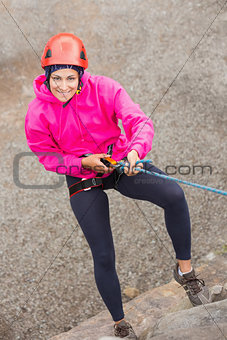 Happy girl abseiling down rock face